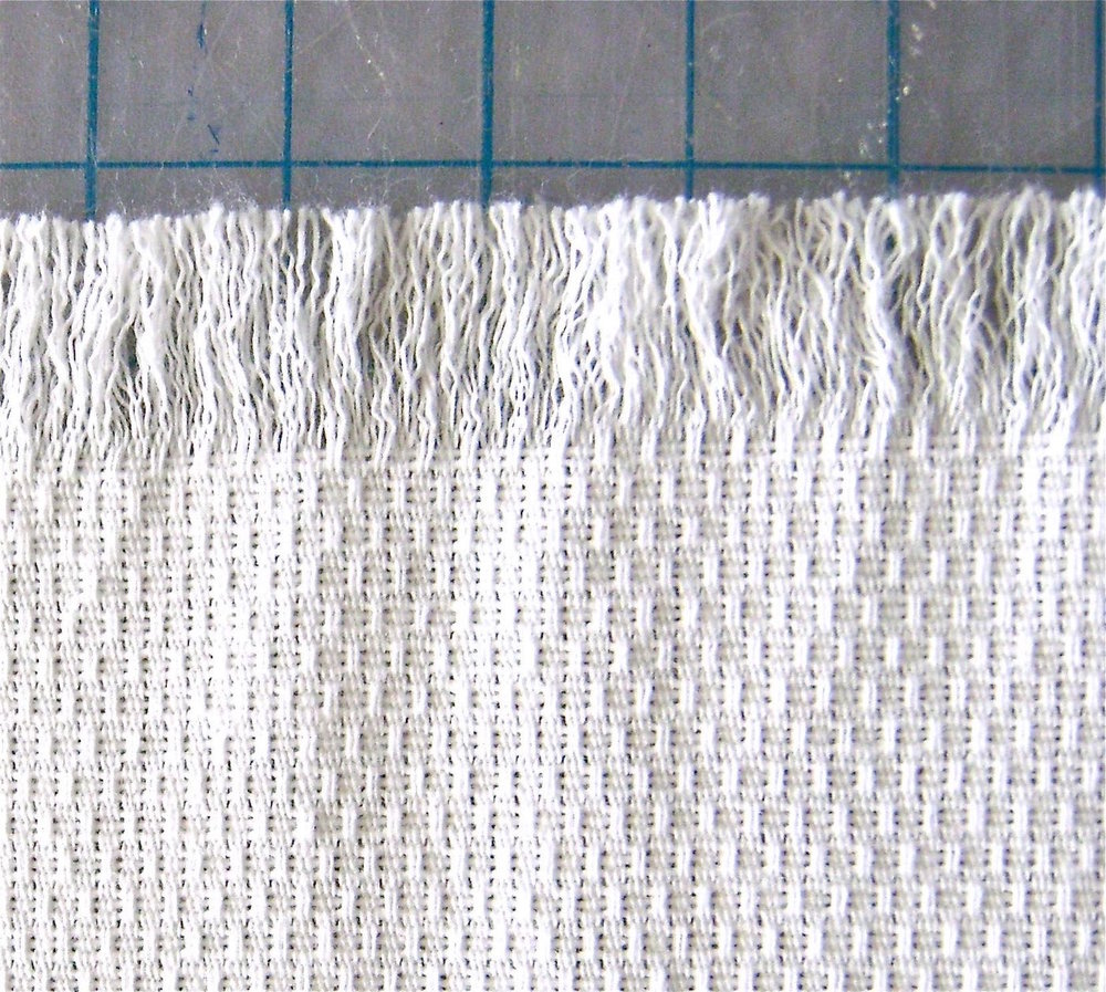 step 2 - Continue to remove more threads until you have a half-inch of fringe.  It's unlikely that the section of fringe will be even so you will need to cut the ends to create a straight edge.