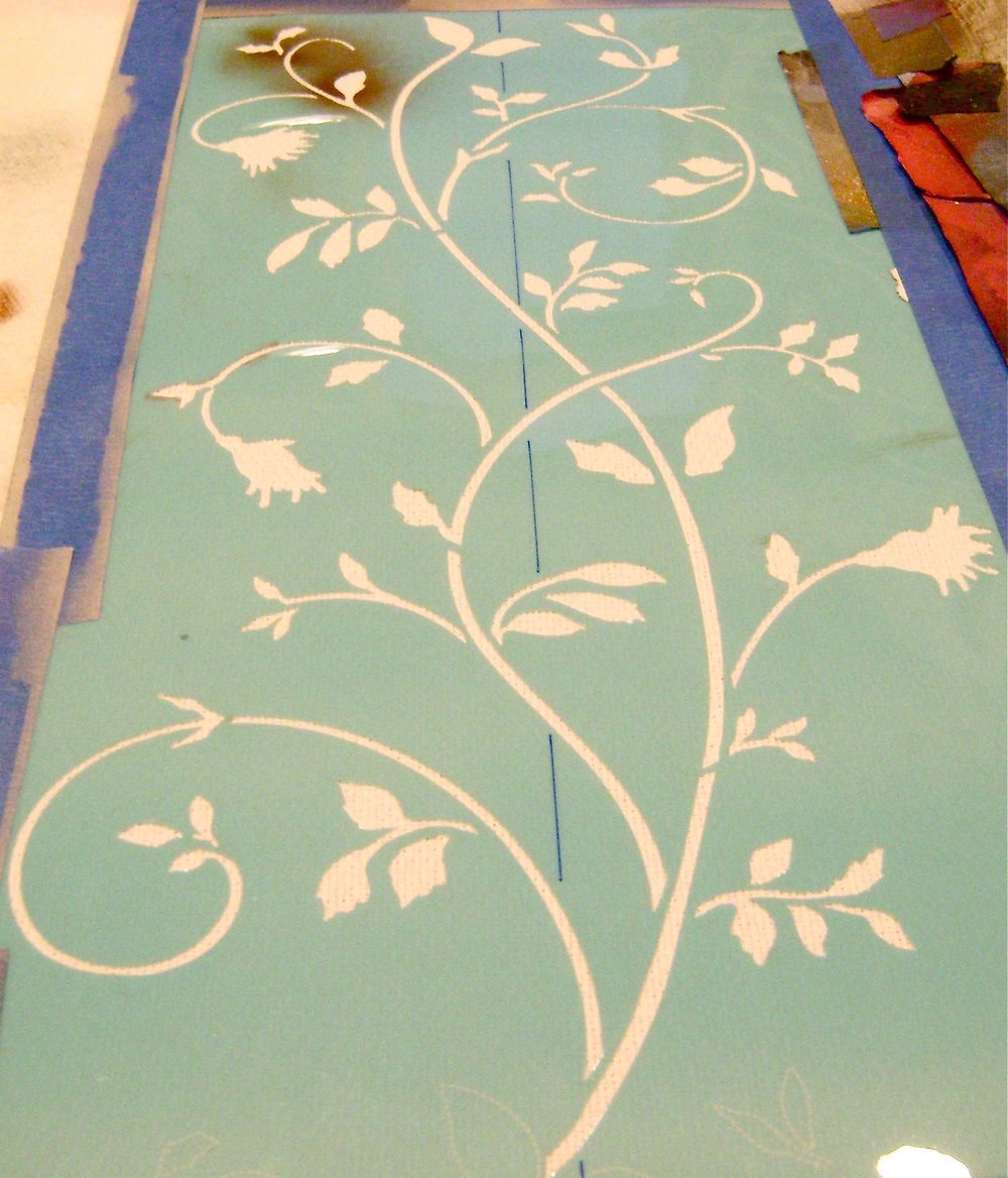 "step 12 - Spray adhesive on the 15"" stencil.  Place it on the runner with the leafy edge 1 ½"" from the border, matching the line on the stencil with the center of the runner.  Paint the large stencil the same way you did the border stencil, applying olive color then adding details with sienna paint.  Remove the stencil and repeat on the other end of the runner."