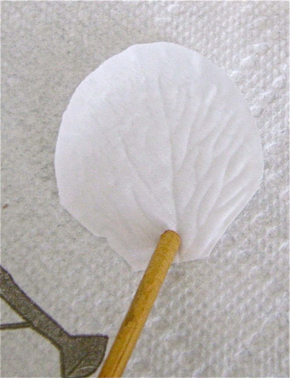 step 2 - Working over a paper towel, use a wood pick to hold down each white petal while you airbrush them.  Paint approximately 80 petals using, red, orange, gold, purple and the tan color you created.