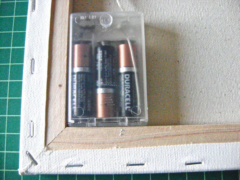 step 12 - Fill the battery pack then tuck it into the lower corner of the canvas' wood frame.  It should be recessed so it will not interfere if the canvas is hung flush to the wall.  Hot glue it in place.  Be sure the control switch is in a convenient position.