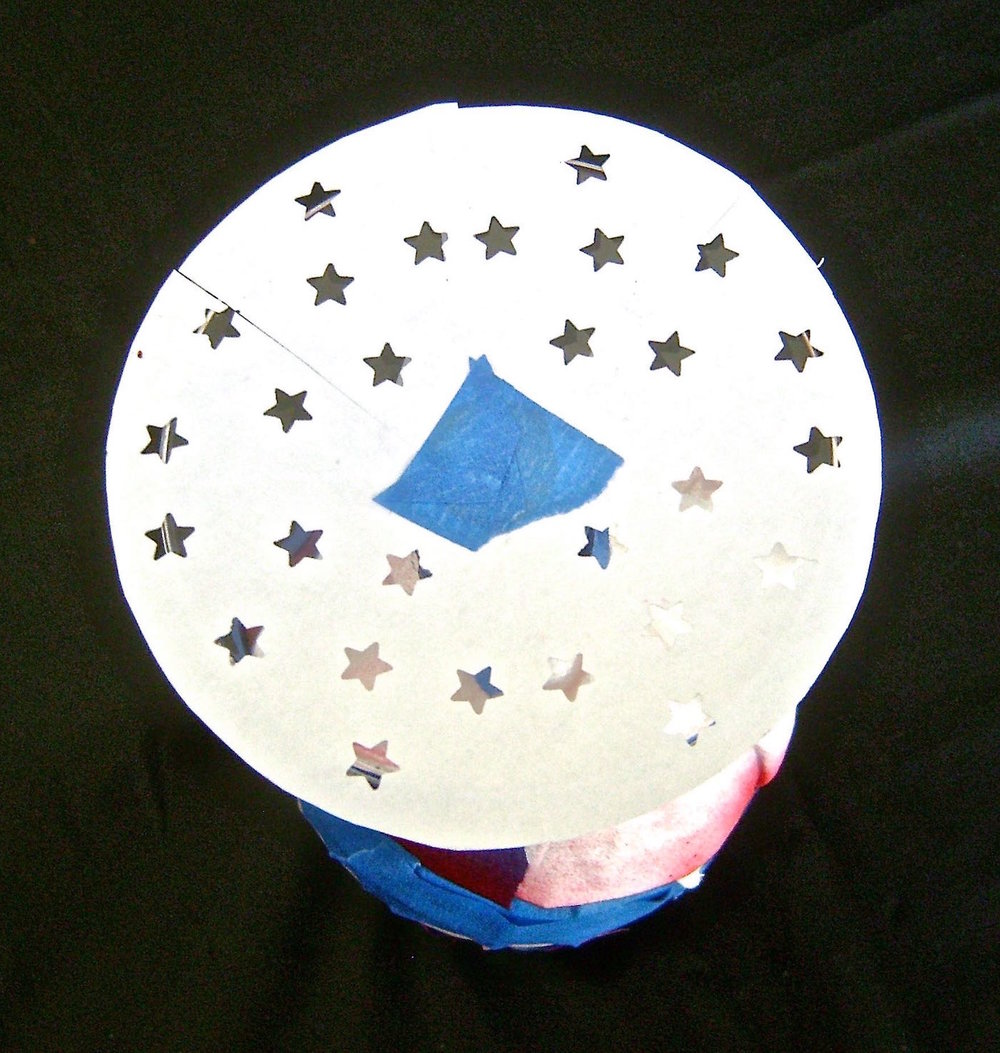 step 5 - Cut a piece of card stock in a circle slightly larger than the glass base.  Fold the circle in fourths.  Use a star paper punch to decorate the circle.  Apply adhesive to one side of the circle and stick it to the glass base.  Protect the rest of the glass from over spray.