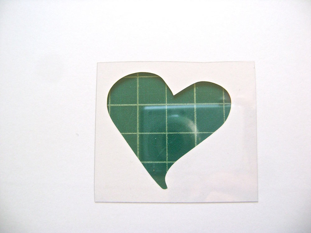 step 2 - Turn the card over. Cut out a clear plastic square slightly larger than the heart hole.