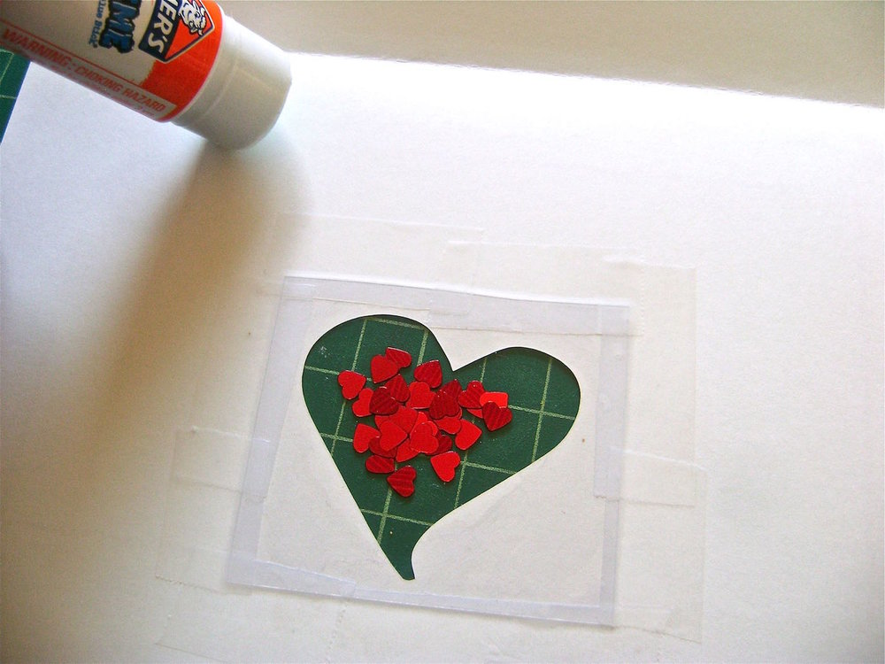 step 5 - With a glue stick, trace around the heart shape on the plastic.  Also use the glue stick to trace the edges of the bottom half of the card and close to the fold. Cut a new sheet of card stock in half and press it to the glued page, aligning the edges.  Press around the heart which will adhere the card stock to the plastic and create a pocket for the hearts.   Allow the glue to set.