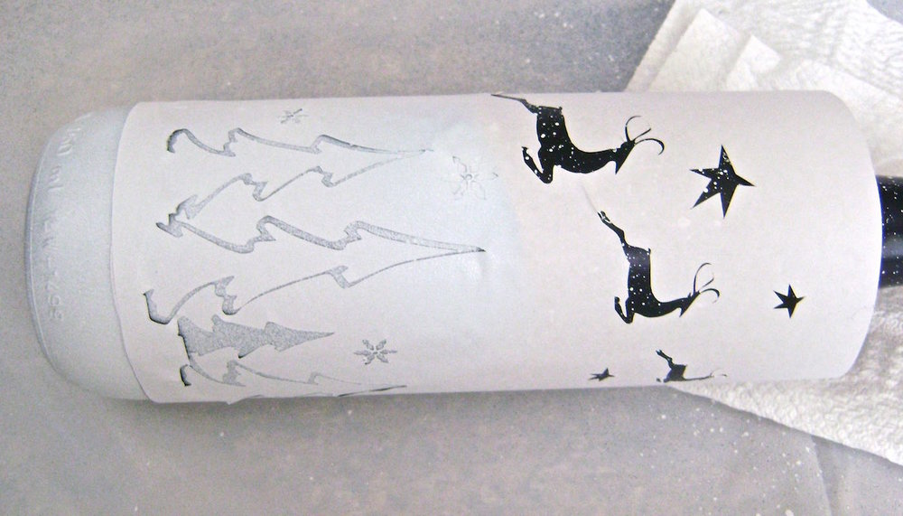 step 6 - When the paint is dry, remove the backing from the stencil sheet for the trees and snowflakes. Press the stencil onto the bottle. Align the bottom of the trees with the rubber band. Cover the reindeer and stars and airbrush the trees and snowflakes with white paint.