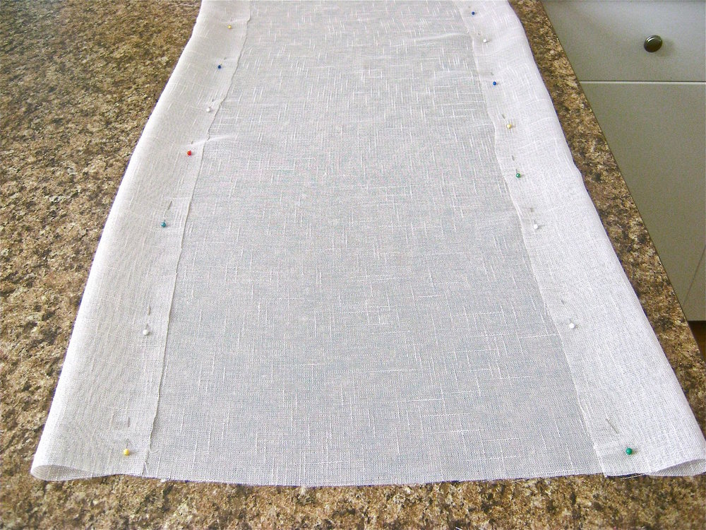 "step 1 - Cut the length and width of the runner you need for your size table. The short finished ends should drop a minimum of 4"" down from the table edge. I made my table runner 18"" wide so that plates on both sides of it would not overlap the fabric or design. For an 18"" runner, start with raw fabric cut to 24"" wide. Fold and pin three-inch hems along each side."