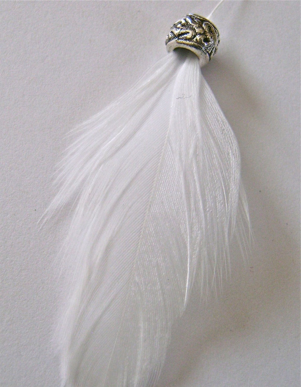 step 4 - Pass the feather's quill through a decorative silver spacer and then into a 10mm pearl.  Push the wire stem up into the spacer and through the pearl with the feather draped across the front side of the wings.