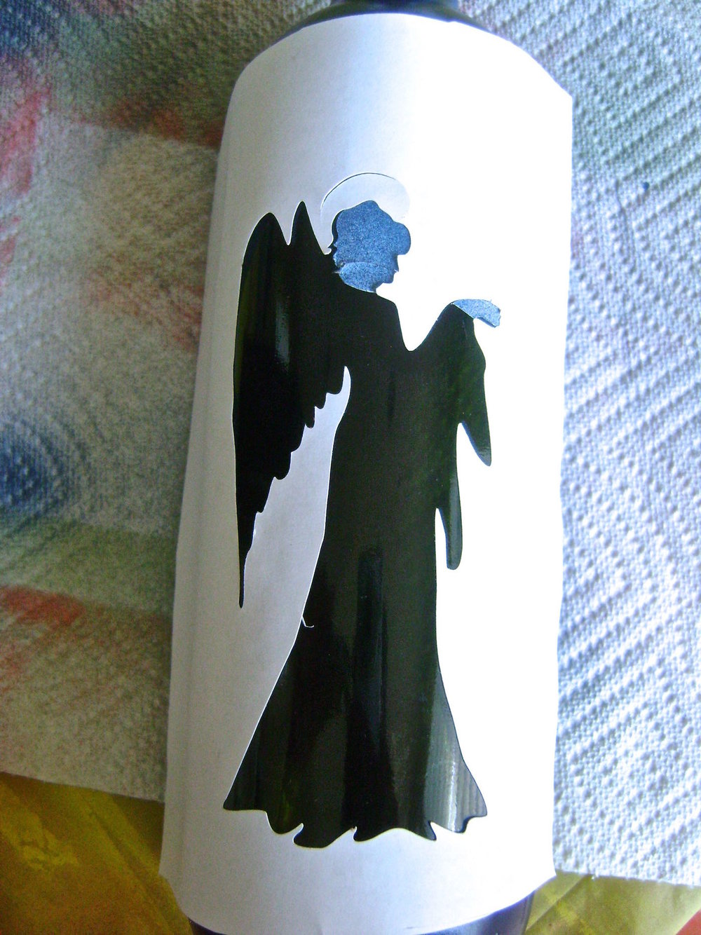 step 6 - Peel off the positive image cutting the stencil to leave the head and hand on the bottle.  Stick the negative stencil in position on the bottle.