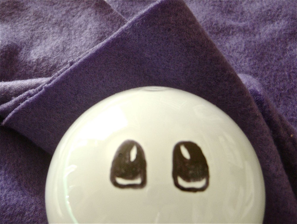step 1 - To keep the bulb from rolling around, cradle it in soft thick fabric, like fleece. Use a thin, black Sharpie to draw the eyes.  Start with the outline of the eyes, then fill in with thicker marker. Don't worry about making mistakes. Any errors can be wiped away with a Q-tip dipped in rubbing alcohol.
