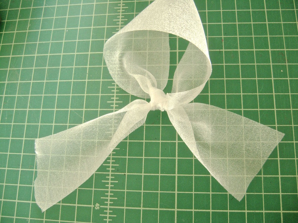 step 10 -  Ribbon Hanger   Make a loop in a piece of sheer ribbon and tie a knot.  Cut off the tails.  Hot glue the knot to the center top of the ornament, hidden behind the fur.