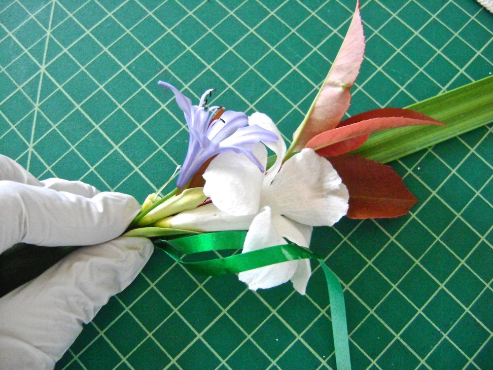 step 3 - Grab a main flower (larger flower) at the base.  Bunch some smaller stems with it and press it to the reed.  Wrap the ribbon around the base twice to catch the flower and stems.