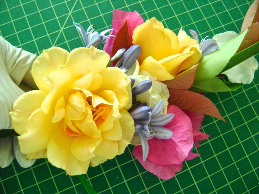 step 4 - Add another flower and stems (be sure to include some greens) and position them to cover the previous wrap.  Wrap the base of the new flower bunch with the ribbon.