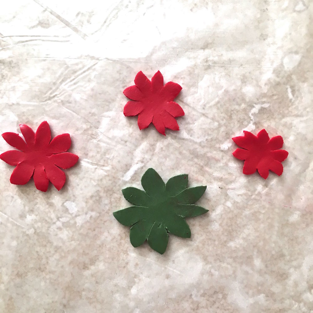 step 3 - You will be creating two poinsettias, one for the front of the ornament and one for the back. Each consists of a green base with three red layers stacked on top. Use the card stock stencil to cut out two green clay pieces from the largest shape. Cut two red clay pieces for each of the three remaining shapes.