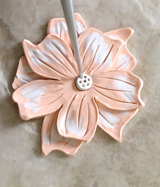 step 10 - Cut out a perfect white clay circle with the Etch N' Pearl tool. Place the circle in the center of the flower. Use the tool's pointy end to create decorative holes in the clay.
