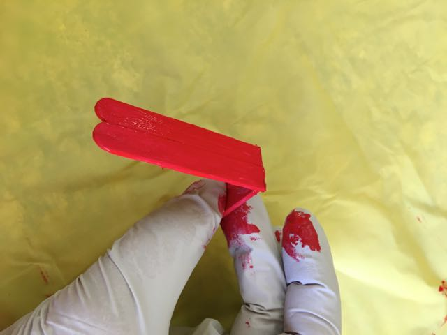 step 5 - Hot glue the straight cut ends together. Paint the craft sticks red for house # 1. The roof on house #2 is painted with a gold metallic enamel marker.
