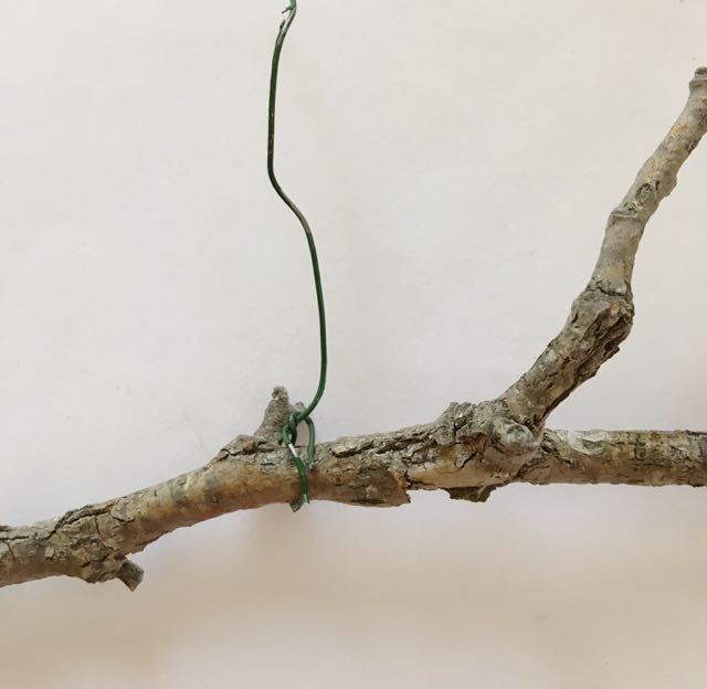 step 22 - Wrap 16 or 18-gauge floral wire around the left and right ends of the top branch to create a hanger.