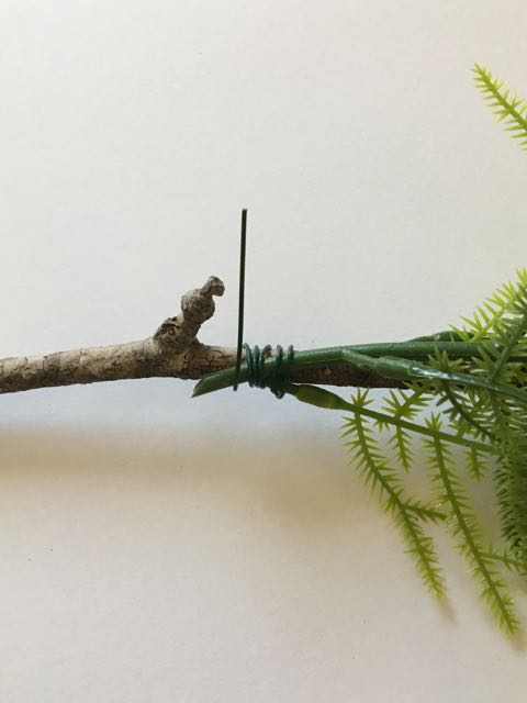 step 25 - Wrap a few greens to the naked branches using 24-gauge wire.