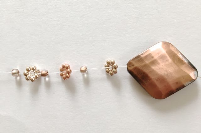 step 4 - Add 11 spacer beads alternating gold and copper with copper lined beads in between each.