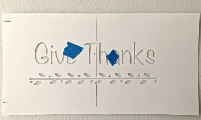 "step 1 - Print out the ""Give Thanks"" message on card stock. With a craft knife or stencil cutting machine, cut out the black areas. Use painters tape to holed the centers of the ""a"" and ""e"" in position. Mark the vertical center to help with alignment."