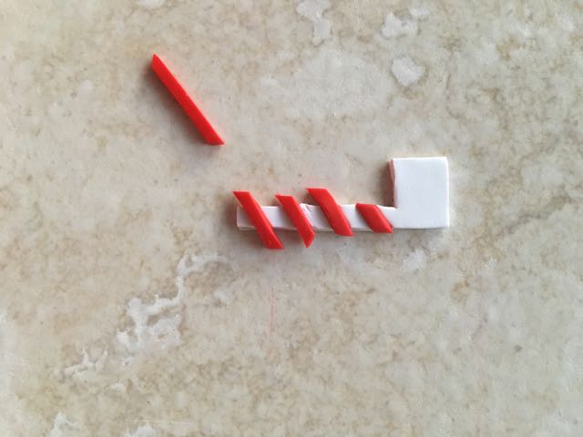 Step 11 - Cut the flag from white clay. Create thin strips of red clay and place them diagonally on the clay post. Roll over them lightly with an acrylic roller to adhere the pieces.
