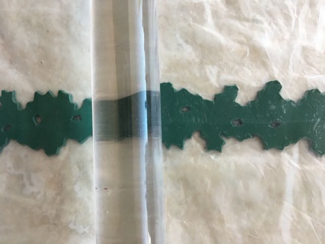 step 3 - Sandwich the clay between deli film. Place an acrylic roller on the film and lightly roll across the surface. Do not apply pressure. This will flatten raises edges but will not change the overall size or shape of the clay.