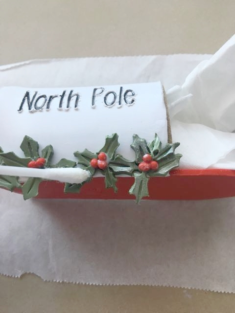 step 16 - Remove the deli film and place the mailbox on parchment paper supported by a ceramic tile. Position the mailbox on its side. Arrange the holly and berries as desired applying Liquid Polymer to the pieces to bond them. Apply Liquid Polymer to the wrong side of the flag and press it to the side of the mailbox. Stuff the center of the mailbox with tissues if necessary to hold it's shape.
