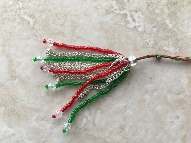 step 4 - Create a total of four red beaded strands and four green. Use green thread for the green beads. Group all the threads together and slip them into a 10mm bead with a large hole. Tie the threads into one knot. Smear adhesive above the beads and chain. Slide the large bead until it is flush with the grouping and covering the adhesive.