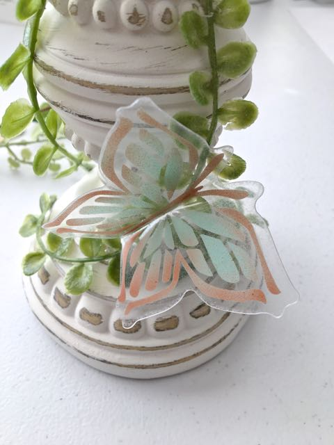 step 14 - Hot glue the butterflies to the greens. Distribute them around the candle pillar on all sides, alternating the sizes and colors.