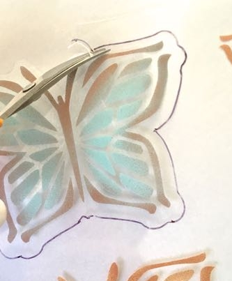 step 10 - With small scissors cut out the butterfly shapes slightly outside the painted edges (see red line on template). You can use the template as your guide by printing it on regular paper, placing the clear sheet on top of the paper, and tracing the red line.