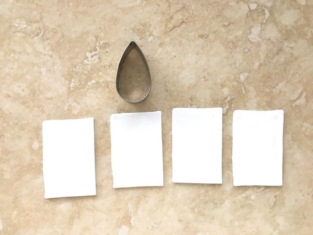 """step 1 - Roll white clay on the #3 setting of the conditioning machine. Cut four rectangles to measure 2.50"""" x 1.50"""" minimum. This will provide a piece large enough for the 1.75"""" long teardrop shaped cutter."""