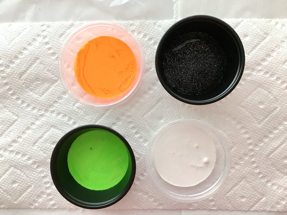 step 2 - Pour approximately one ounce of each paint color into small disposable plastic containers – Orange, Black Ice, Alien Green, and White. Pour about two ounces of Black paint for the base color in a separate container. Add Testors Marbling Medium to each container in a 50/50 ratio.