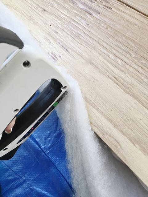 step 10 - Bring the batting to the back of the plywood and staple it close to the edge of the wood. Work around the corners feeding in excess batting to create a clearly visible corner.