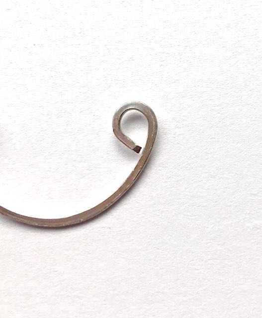 step 8 - Flatten the three curved wire shapes with the chasing hammer. The curls may tend to open slightly. After they are flattened, close them with flat nose pliers.