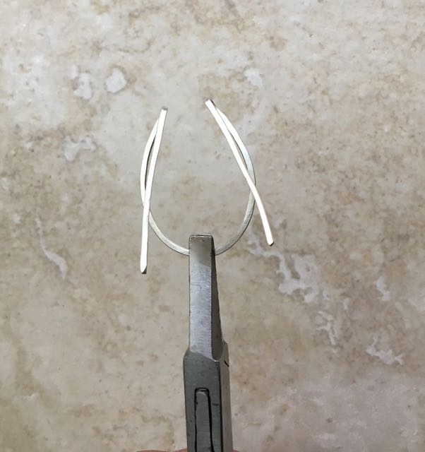 """step 5 - Hold the wire with flat nose pliers over the center mark and pinch the folds closer together. There should be approximately 3/8"""" in between them."""