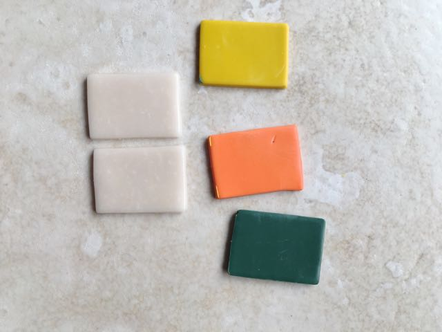 """step 4 - To create the """"gem"""" cut out a single one inch square or rectangle from yellow, orange, and green clay. Cut out two pieces of the translucent clay."""