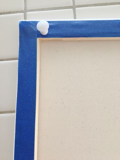 step 1 - For a clean canvas back, tape the edges. Use extra large pushpins in each corner to keep the canvas level. A crooked canvas will cause paint to shift, possibly in unwanted ways.