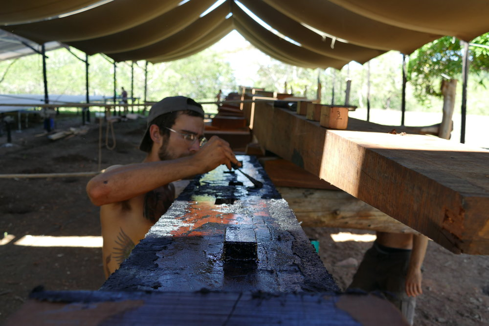Fred applying tar to the coaxes and scarves of the keel of  Ceiba . Photo by Finn Richardson.