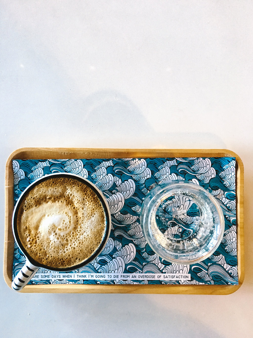 """There are some days when I think I'm going to die from an overdose of satisfaction."" My macchiato came on this adorable plate with a picture and a quote on it."