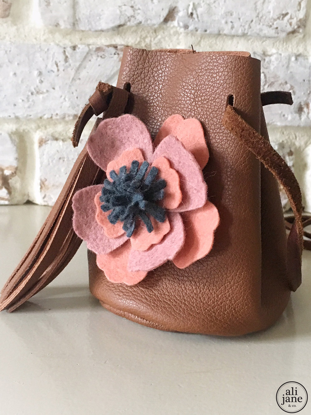 Small brown leather cross body bucket bag with tassel