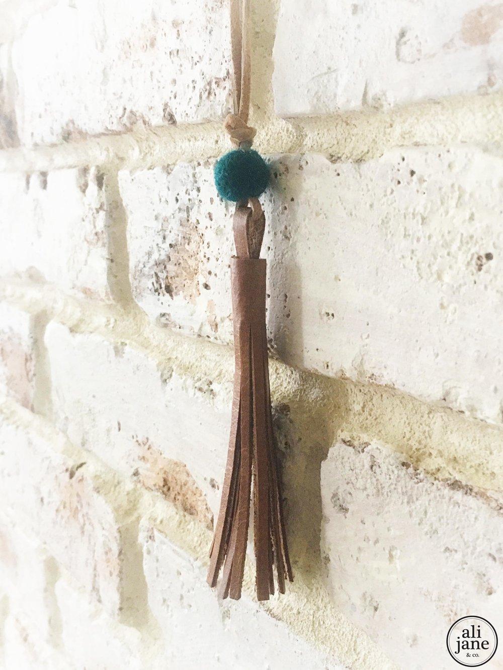 Little girls tan tassel necklace with peacock wool felt pom pom