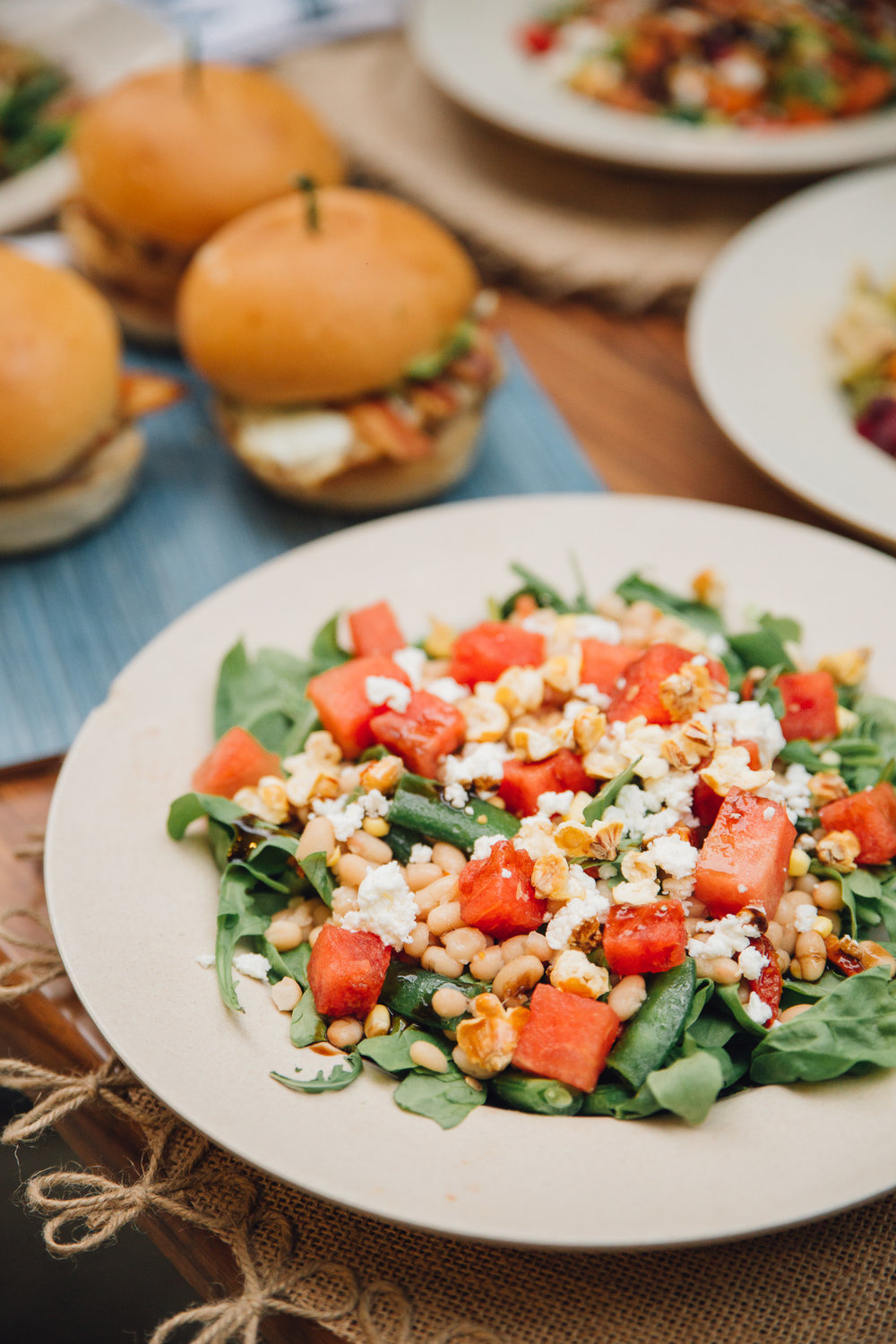 Ingredients:watermelon, feta, arugula, baby spinach, white bean salad (cannellinis, snap peas, corn, sun dried tomato), toasted corn, mint, balsamic glaze, red wine vinegar and olive oil.