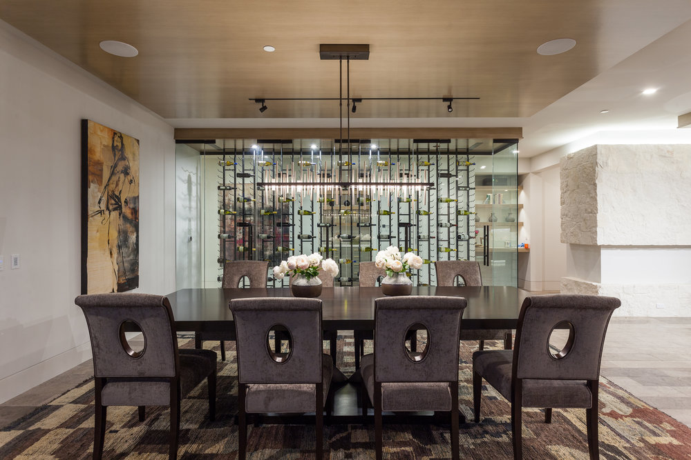 The dining room's enclosed, climate-controlled floor-to-ceiling glass wine cellar spans approximately 25 linear feet and has room for 1,000-plus bottles