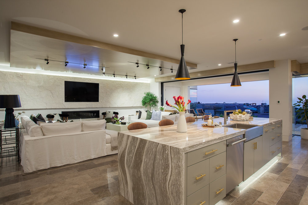 The home'skitchen and family room open to mesmerizing ocean views and a partially covered terrace via Fleetwood pocket doors