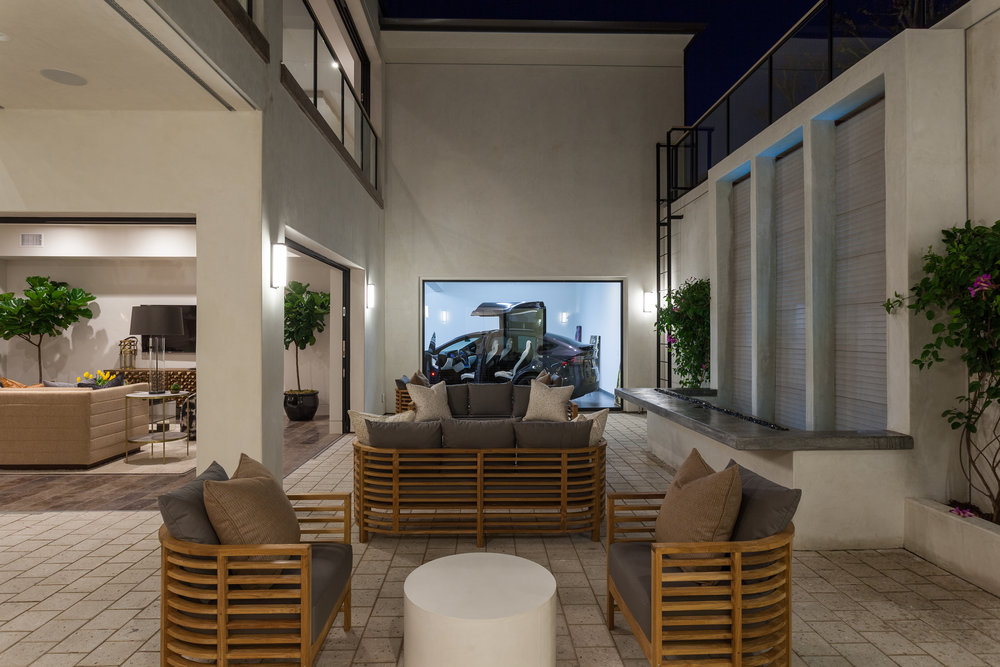A private courtyard offers a seating area, 20-foot waterfall, linear fire pit and a massive window into the garage that allows a car-lover to exhibit a favorite automobile