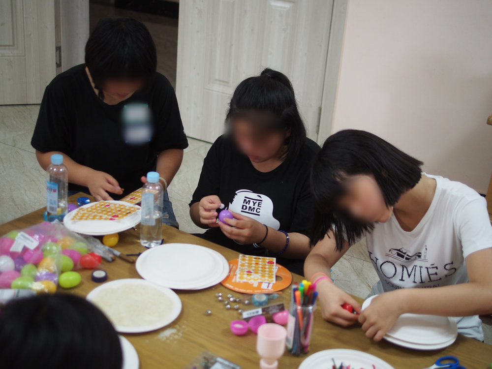 Sung Me (center) working on crafts at our annual retreat for North Korean orphans.