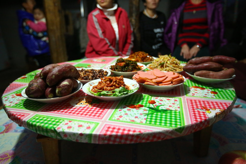 A group of North Korean women and their children prepare a meal for us during one of our visits.