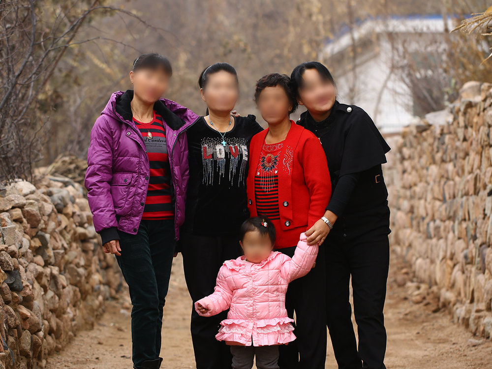 Four North Korean refugee women with one of their children born from a forced marriage.