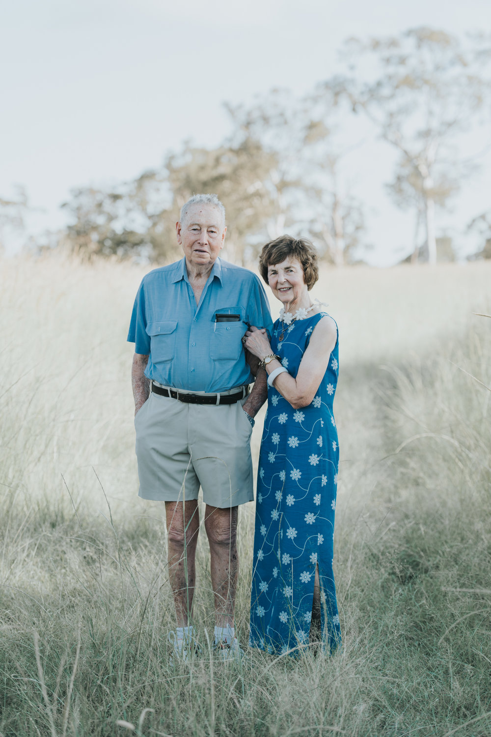 Elderly couple embracing in long grass | Sirromet Winery | Lightsmith Images