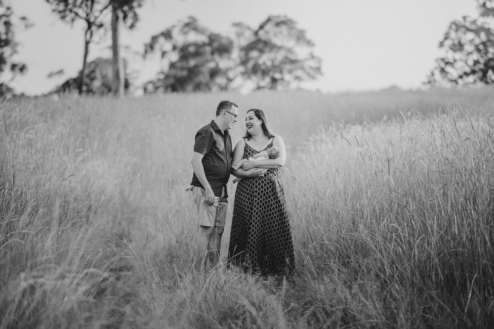 Black and white photo of mother and father with baby in a field | Sirromet Winery | Lightsmith Images
