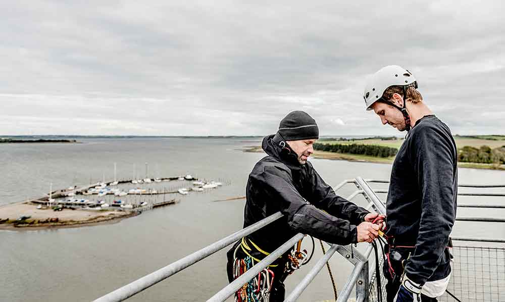 Vores instruktør Jakob Vemmelund forbereder en kunde på rapelling på toppen af tårnet på Doverodde Købmandsgård.