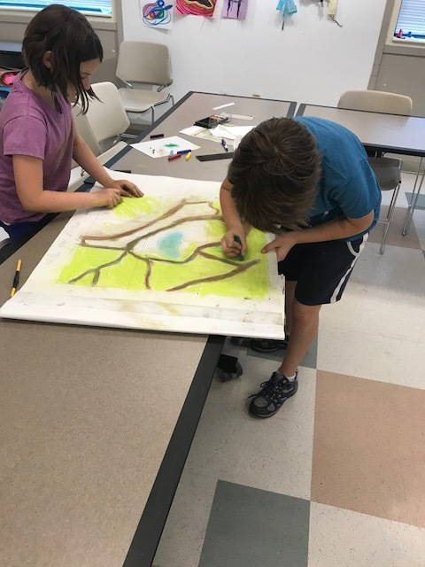 Students work together to color the background of a tree map.